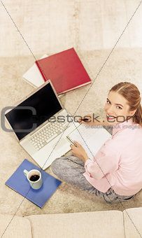 Top view of smiling young girl studying sitting on carpet.