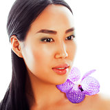 young pretty asian woman with flower purple orchid closeup isola