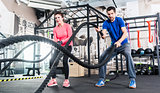 Woman and man in gym functional training with battle rope