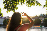 Woman hands showing shape of a heart on sunset, young woman travel alone, love concept.