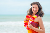 Happy young brunette in pareo and flower lei against the sea