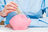 Close-up of a pink piggy bank and a hundred dollar money stock