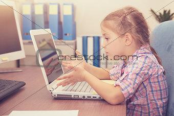 Little girl doing homework on the laptop