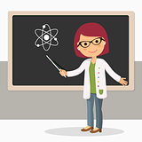 Young female teacher on science lesson at blackboard in classroom