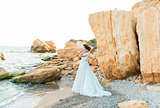 Romantic beautiful bride in luxury dress posing on the beach.