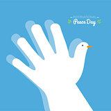 International peace day with hand making the shape of a dove on a blue sky background