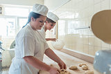 Women in bakery forming raw dough to pretzels