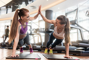 Two beautiful women giving high five while practicing basic plan