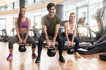 Three fit young people exercising kettlebell swings during full-