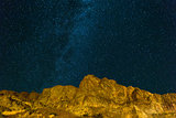 Starry Night Sky over Rocky Landscape