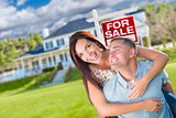 Playful Excited Military Couple In Front of Home with For Sale R