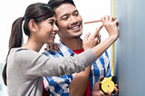Young indonesian couple measuring walls in new apartment