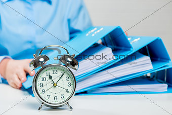 Close-up alarm clock and business documents out of focus