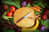 Fresh raw vegetable ingredients for healthy cooking or salad making with wooden cutting board in center, top view, copy space. Diet or vegetarian food concept