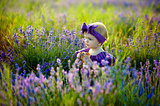 Cute child girl walking in lavender field, happy childhood concept