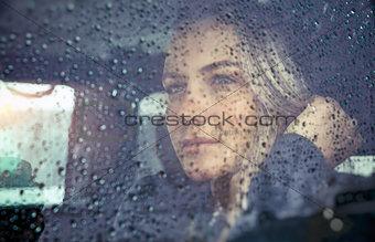 Beautiful sad woman in the car