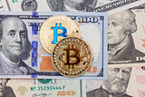 Bitcoins on money bills background.