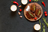 Tasty barbecue steaks and beer in glasses on a black stone background, with cherry tomatoes and chili peppers