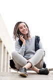 Attractive and smiling teenager girl relaxing with a skateboard and sitting down, talking to somebody on phone