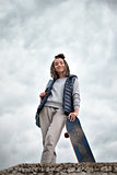 Beautiful hipster girl with skate board standing with smile