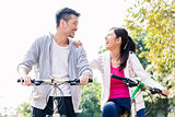 Young Asian couple laughing together while riding bicycles
