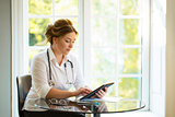 Young medical doctor woman seating at the table with sthetoscope and looking to the tablet