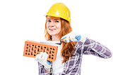 woman builder with a brick in a yellow hard hat against a white
