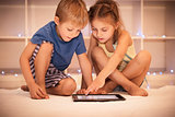 Two happy children playing on the tablet