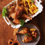 Grilled chicken quarter with potato for garnish. Top view. Wooden background
