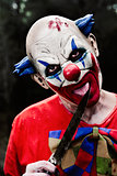 scary evil clown with a knife in the woods