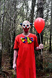 scary evil clown with a red balloon in the woods