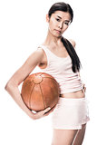 Young fit Asian woman holding brown medicine ball