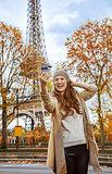 elegant woman in Paris, France taking selfie with phone