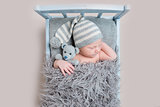 newborn baby sleeping on a bed