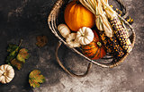 Different pumpkins and corn in a in basket.