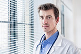 Portrait of a young serious doctor looking at camera with determ