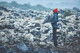 Woman hiker walks on volcanic Lava fields on background of mountains of Iceland.