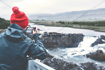 a woman photographing a waterfall on phone