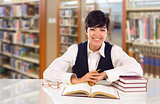 Young Female Mixed Race Student In Library with Books, Paper and