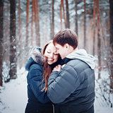 Young loving couple embracing in winter forest