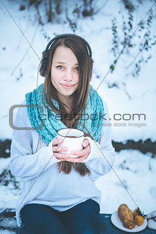 Beautiful woman drinking hot drink in winter park