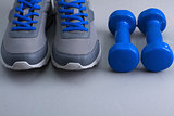 Sport equipment - sneakers and dumbbells on gray background.