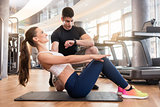 Personal trainer timing young fit woman during isometric exercis