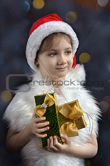 Little girl in hat of Santa Claus with gifts in his hands, colorful bokeh