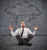 Businessman practice yoga under a rainy cloud