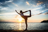 Fit woman practicing on the beach the standing bow pulling pose