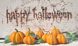 Happy Halloween greeting with pumpkins and green leafs on wooden