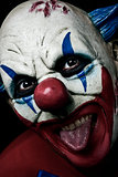 scary evil clown taking out his tongue