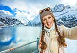 smiling young woman in winter Alto Adige, Italy taking selfie
