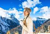 tourist woman against mountain scenery with thermos travel mug